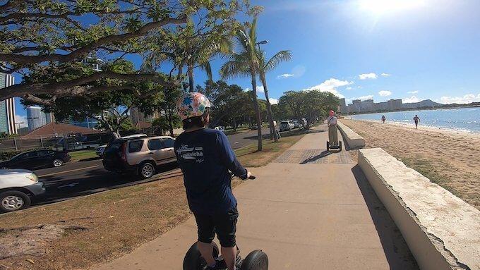 セグウェイでアラモアナ・ビーチパークの海沿いを走る様子